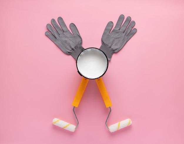 Creatieve compositie van verfrollers, open blik witte verf en werkhandschoenen. visualisatie van gelukkig man met opgeheven handen huisreparaties doen.