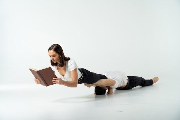 Creatieve compositie van vrouw evenwicht houden op man's handen en boek lezen
