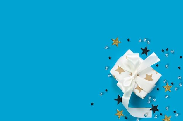 Creatieve compositie van witte geschenkdoos met wit lint en kleurrijke sterren met glanzende diamanten op blauw met kopie ruimte plat lag bovenaanzicht