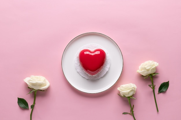 Creatieve compositie voor valentijnsdag met rood hart cake en bloemen