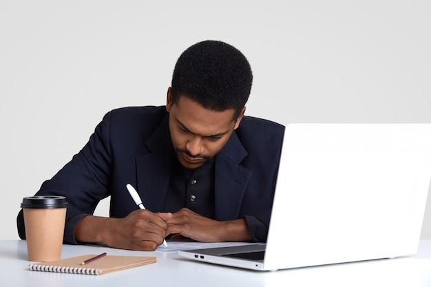 Creatieve copywriter schrijft ideeën op, zit voor geopende laptopcomputer, omringd met blocnote, dispoasable kop warme drank, poses op de werkplek, geïsoleerd op wit.
