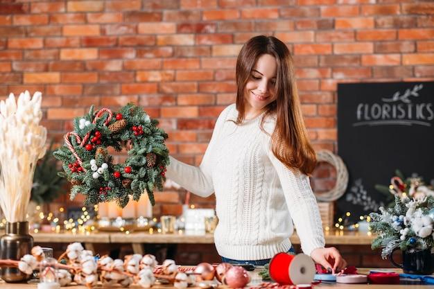 Creatieve dame fir tree krans houden, glimlachend.