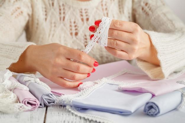 Creatieve diy hobby. handgemaakt ambacht met kant maken. de vrije tijd van de vrouw, vrouwelijke handenclose-up die aan witte houten lijst werken