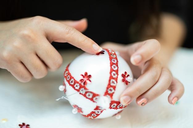 Creatieve doe-het-zelf hobby. het maken van handgemaakte ambachtelijke witte stijlvolle kerstballen met kant.