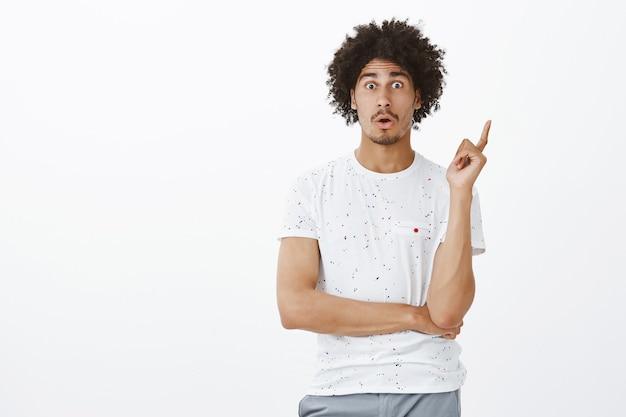Creatieve donkerhuidige man die vinger in eureka-gebaar opheft, met interessant idee