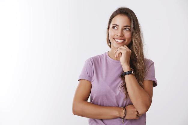 Creatieve, dromerige, energieke jonge aantrekkelijke vrouw die denkt welk cadeau een beeldvormingsvriendreactie koopt en er opgewonden uitziet, merkwaardig linksboven in de hoek glimlachend, kin aanrakend, idee witte muur hebbend