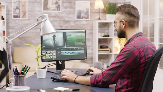 Creatieve filmmaker die thuis werkt aan de postproductie van een film. vriendin op de achtergrond loopt in het huis en praat aan de telefoon.