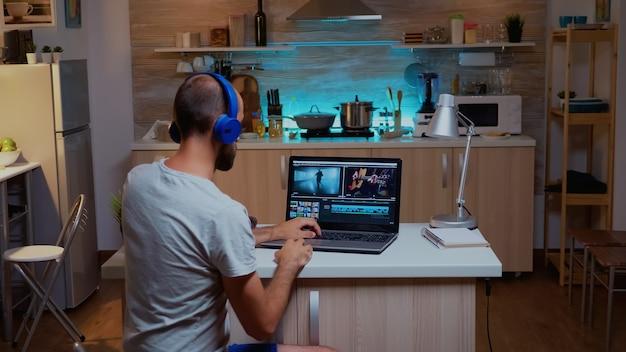 Creatieve filmmaker die videobeelden thuis bewerkt met behulp van moderne technologie. man contentmaker in huis werkt aan montage van film in nieuwe software om 's avonds laat te bewerken.