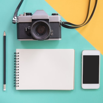 Creatieve flat lay ontwerp van reisconcept met lege notebook, potlood, camera en mobiele telefoon op gele en groene pastel kleur.