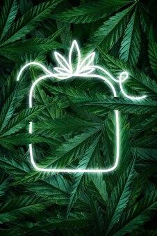 Creatieve fluorescerende kerstachtergrondlay-out van hennepbladeren, marihuana en neonreclamegeschenk