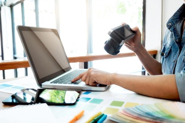 Creatieve fotograaf selecteert foto's en gebruikt de computer om te werken.
