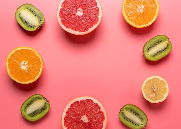 Creatieve fruitsamenstelling op roze achtergrond met harde schaduwen