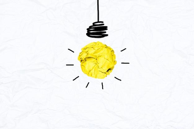 Creatieve geelgeel verfrommeld papier gloeilamp op witte recycle papaer achtergrond.