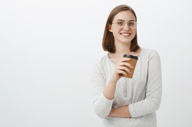 Creatieve gelukkig en enthousiaste charmante vrouwelijke kantoormedewerker met pauze staande in café over grijze muur met papieren kopje koffie praten geamuseerd met collega glimlachen