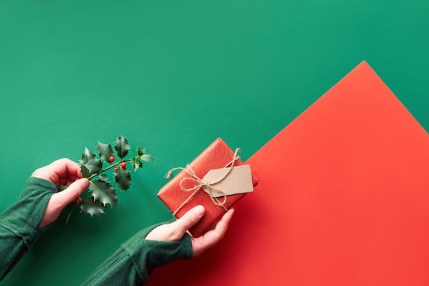 Creatieve geometrische plat lag op groen en rood papier. vrouwelijke handen die verpakte gift en takje hulst met rode bessen houden. eco-vriendelijke cadeau-ideeën voor kerstmis zonder afval.