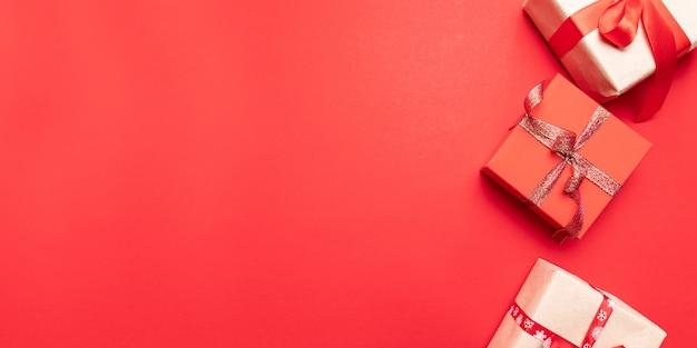 Creatieve geschenken of presenteert dozen met gouden bogen en ster confetti op rode bovenaanzicht. plat lag compositie voor verjaardag, kerst of bruiloft.