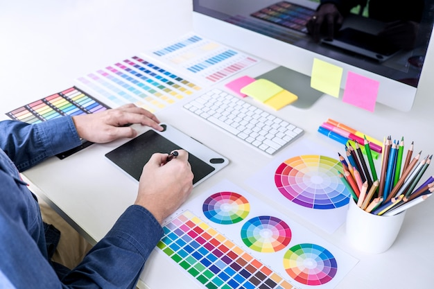 Creatieve grafisch ontwerper werkt aan kleurselectie en kleurstalen, tekening op grafisch tablet