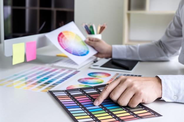 Creatieve grafische ontwerper die aan kleurselectie werkt en op grafiektablet trekt op het werk