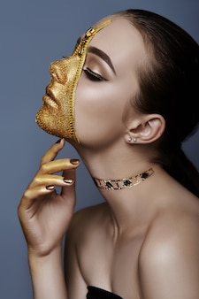 Creatieve grimmige make-up gezicht van vrouw met gouden kleur rits kleding op huid
