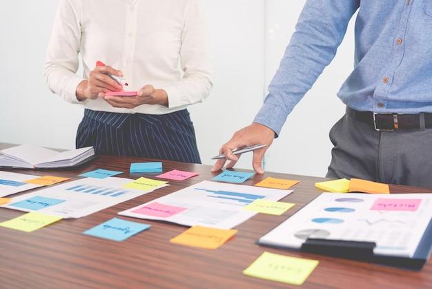 Creatieve groep zakenmensen brainstormen gebruiken plaknotities plukken om idee op tafel te delen.