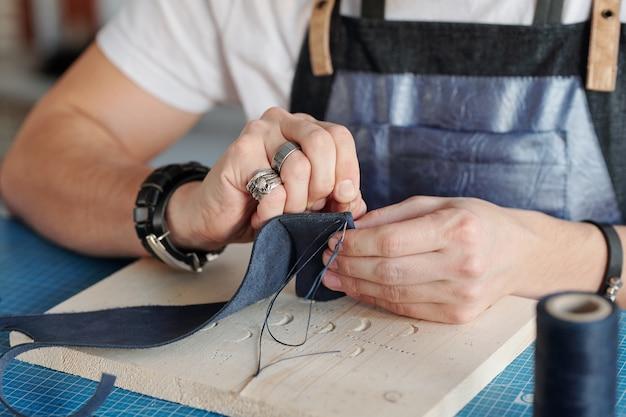 Creatieve handwerkmeester met naald die een klein stukje zwart suède over een houten bord op tafel houdt terwijl hij iets naait