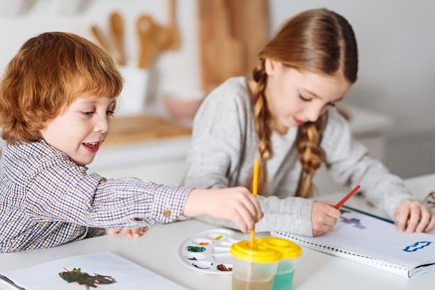 Creatieve hemel. bewonderenswaardige lieve getalenteerde kinderen die aan tafel in een keuken zitten en dingen tekenen terwijl ze de ochtend samen doorbrengen