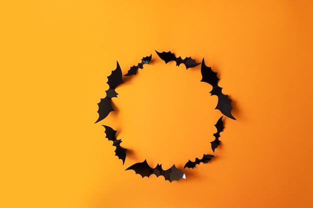 Creatieve herfst halloween compositie van zwart papier vleermuizen frame op een oranje achtergrond