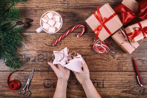 Creatieve hobby. de handen van de vrouw tonen met de hand gemaakt de kerstboomstuk speelgoed van de kerstmisvakantie.