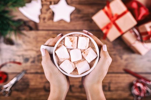 Creatieve hobby. de handen van de vrouw tonen mok cacao met marshmallows