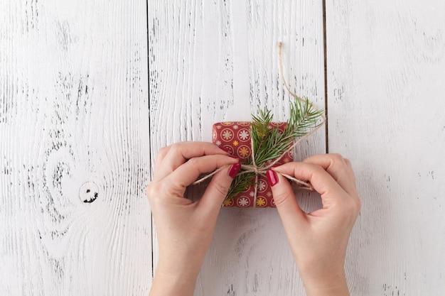 Creatieve hobby. de handen van de vrouw verpakken het met de hand gemaakte heden van de kerstmisvakantie in ambachtdocument met touwlint. het maken van boog op xmas geschenkdoos