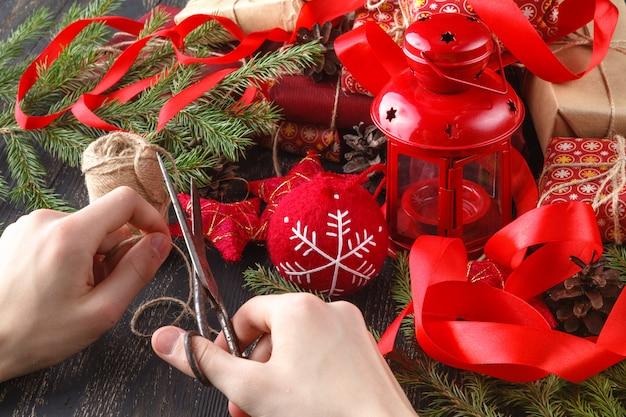 Creatieve hobby. handen omwikkelen handgemaakte kerstcadeau in ambachtelijk papier met touw lint