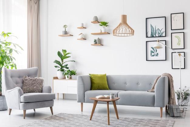 Creatieve houten hanglamp boven een grijze bank en een comfortabele fauteuil in een scandinavische woonkamer