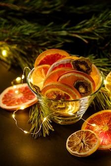 Creatieve humeurige vakantie kerstmis nieuwjaar voedsel fruit met gedroogde grapefruit, kiwi, sinaasappel en citroen in glazen kom met tak van dennenboom met warme led-verlichting, hoekmening