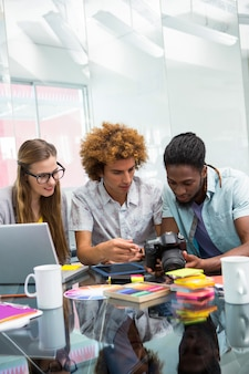 Creatieve jonge bedrijfsmensen die digitale camera bekijken