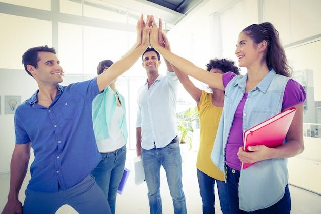 Creatieve jonge bedrijfsmensen die hun handen samenbrengen