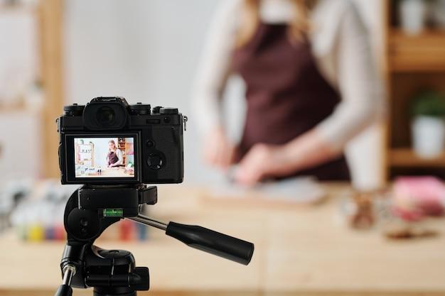 Creatieve jonge vrouw die in huiscamera zeep maakt die masterclass maakt voor haar abonnees