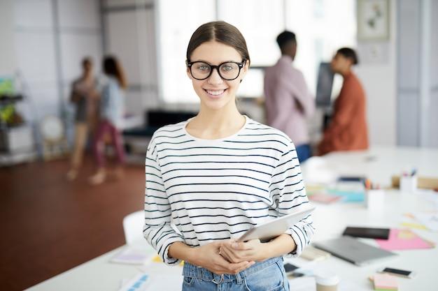 Creatieve jonge vrouw poseren in office