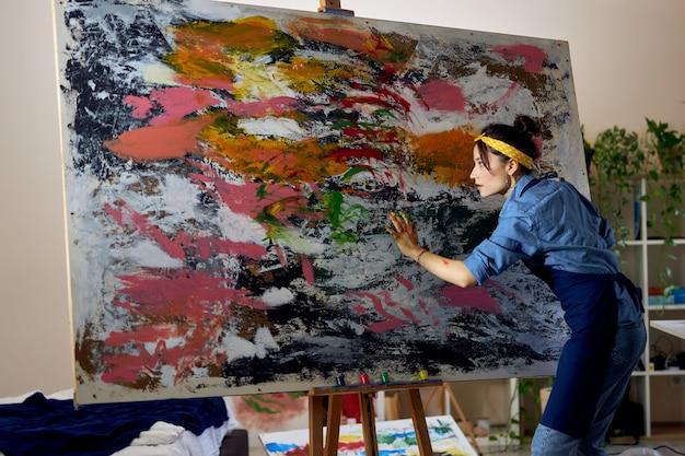 Creatieve jonge vrouwelijke schilder die aan een groot modern abstract olieverfschilderij werkt dat verf aanbrengt