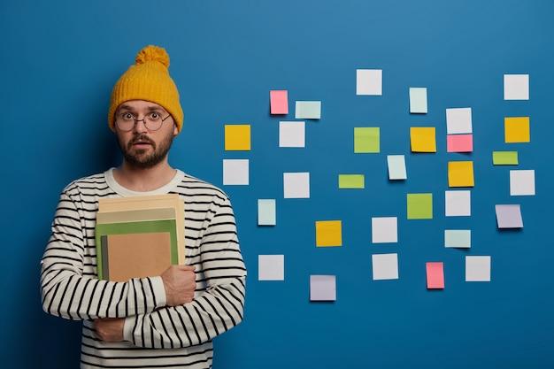 Creatieve jongeman werkt in stijlvolle zolderruimte, ziet er verrassend uit, draagt stijlvolle kleding, houdt dagboek en schoolboeken vast, plant zijn volgende project