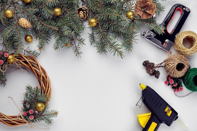 Creatieve kerst diy vrouw die handgemaakte kerstkrans maakt thuis vrijetijdsgereedschap snuisterijen en details voor...