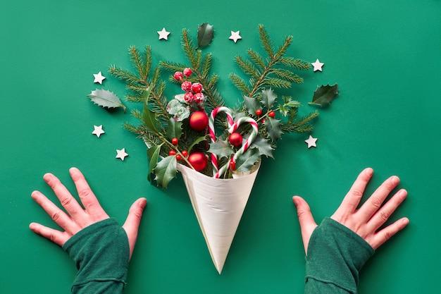 Creatieve kerst plat lag op groenboek. handen en kerstversiering in fineerkegel - sparren en hulsttakjes, kerstballen, zuurstokken, houten sterren en rode bessen.