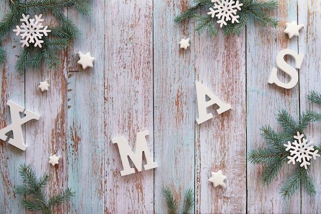 Creatieve kerst plat leggen met witte letters xmas op rustieke houten planken.