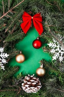 Creatieve kerst samenstelling gemaakt van fir tree takken in kerstboom vorm met dennenappel en kerstballen met lint en sneeuwvlokken op groene houten verticale lay-out plat leggen