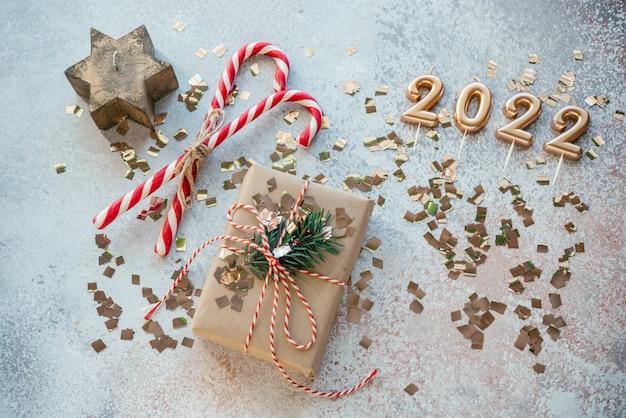 Creatieve kerstachtergrond met geschenkdoos, zuurstokken en kerststerkaars en 2022-nummers