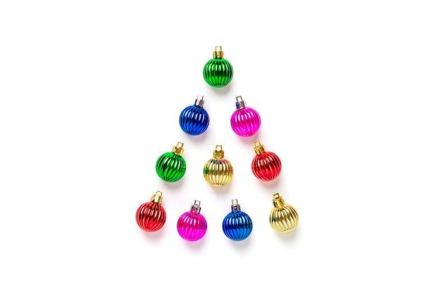 Creatieve kerstboom die van kleurrijke snuisterij en gouden sterdecoratie wordt gemaakt die op witte achtergrond wordt geïsoleerd.