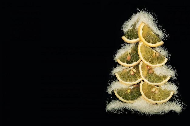 Creatieve kerstboom gemaakt van plakjes citroen op een zwarte achtergrond. sneeuw is als suiker. vakantie-cards.