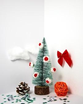 Creatieve kerstboomcompositie in driedimensionale ruimte met decoraties bloemen wolken muur vooraanzicht