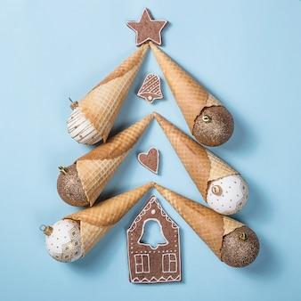 Creatieve kerstindeling. kerstboom gemaakt van feestelijke hoorns met glanzende ballen