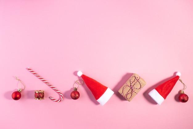 Creatieve kerstlay-out gemaakt van kerstmanhoed en decoratie op roze. minimaal winter plat kerstconcept. kerstmis nieuwjaar plat lag.