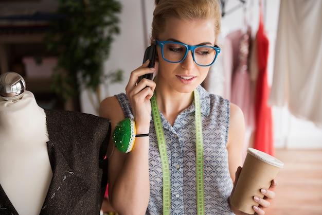 Creatieve kleermaker praten via mobiele telefoon